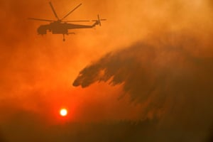 Athens, Greece A helicopter releases gallons of water as it attempts to extinguish a wildfire near the village of Metochi. The blaze has ripped through thousands of hectares of pine forest. See our wildfires across souther Europe gallery