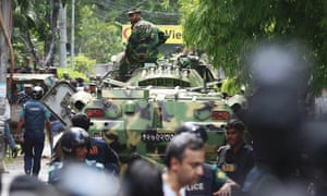 Bangladeshi soldiers and security personnel sit on top of armoured vehicles in a diplomatic zone of the capital, Dhaka.