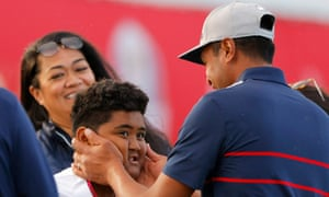 Tony Finau celebrates with family on the 15th green after winning the match.