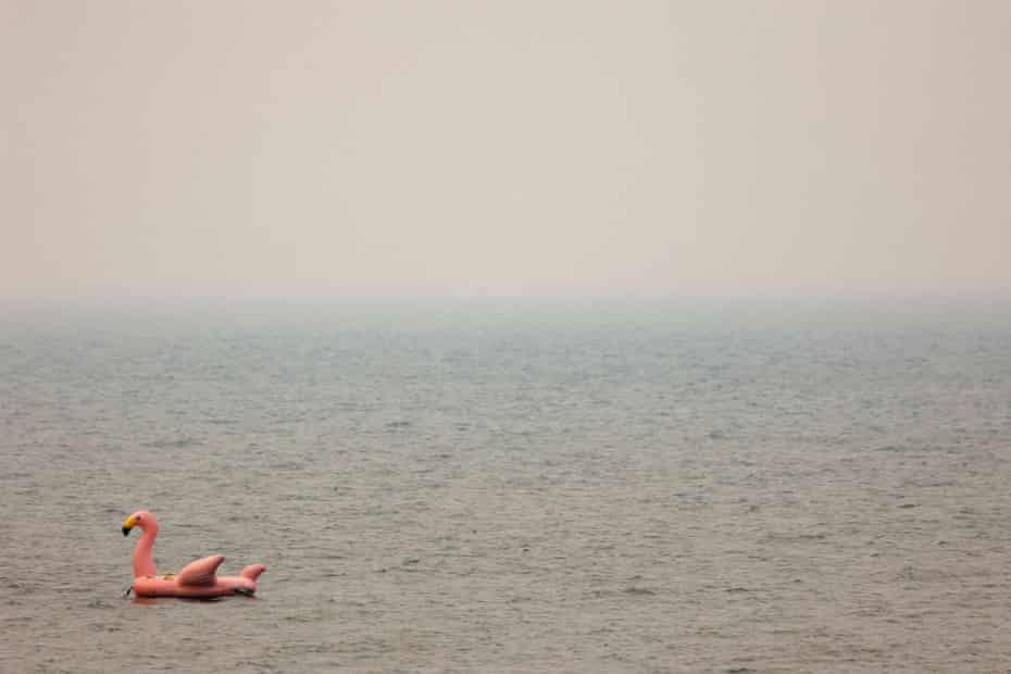 A giant inflatable flamingo floats on Lake Tahoe as smoke from the Caldor fire is thick in the air.