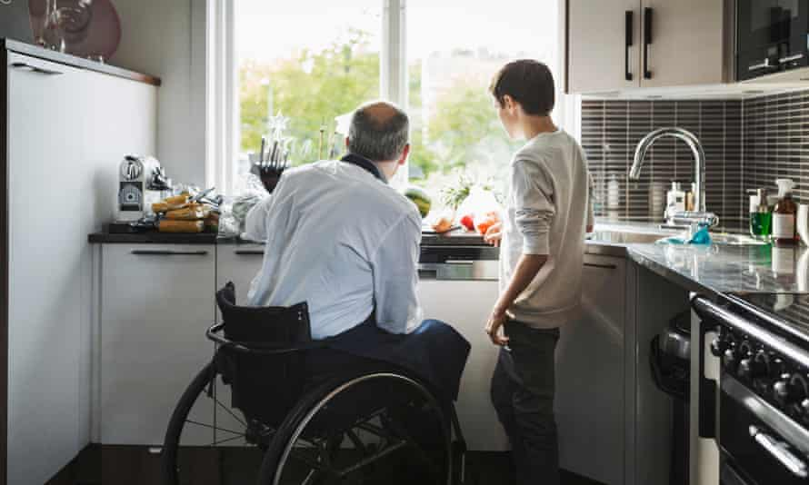 A disabled father and his son in the kitchen