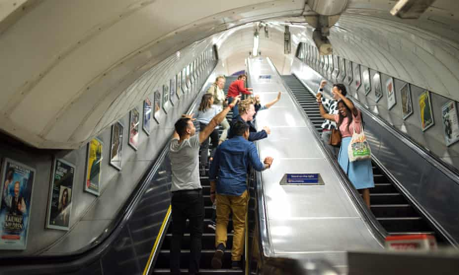 Groups of passengers cheer and sing about the night tube on the Oxford Circus escalators. Alex and Ibbi are on the right.