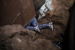 Andrea Nicole Arita from Honduras, part of a caravan of thousands from Central America trying to reach the United States, crawls through a hole under the border wall to cross illegally from Mexico to the U.S in Tijuana.