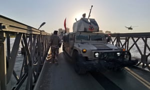 Iraqi solders next to an armoured vehicle in Mosul