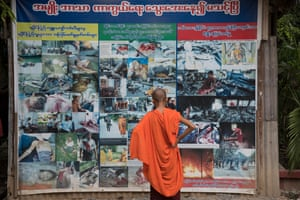 A Buddhist novice looks at pictures outside Ashin Wirathu's quarters showing atrocities allegedly committed by Muslims against Buddhists