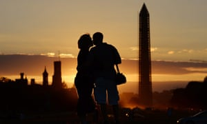 A couple kiss at sunset by the Washington Monument.