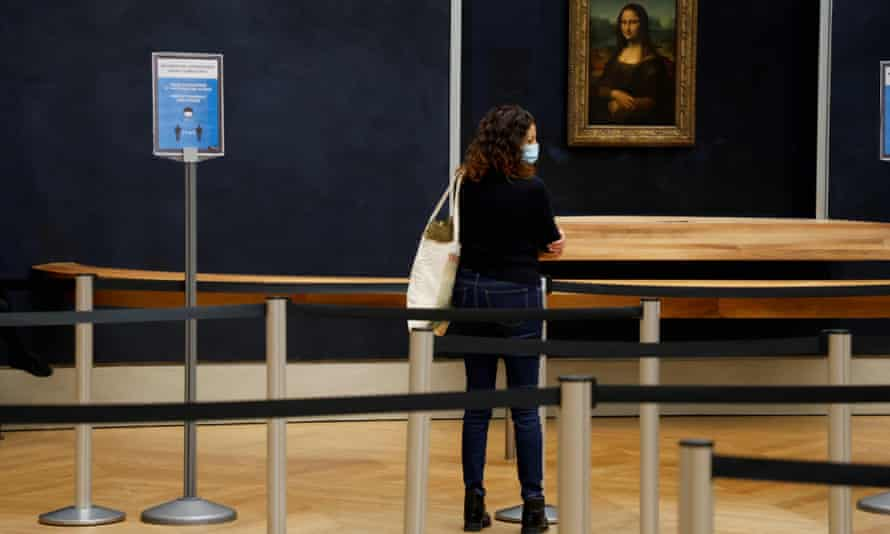 A woman wearing a mask stands alone in front of the Mona Lisa next to a sign urging social distancing