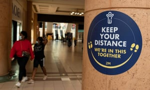 People pass a sign warning about social distancing in the Spindles shopping centre in Oldham, Greater Manchester.