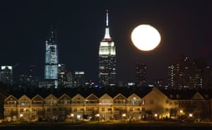 Jersey City, US The moon rises behind the Empire State Building in New York City and homes in Jersey City, as seen from Newark