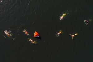 People swim in West Reservoir in Stoke Newington, north London