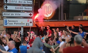 A flare is waved by an England fan in Lille city centre, France, as fresh clashes have taken place between rival groups of supporters.