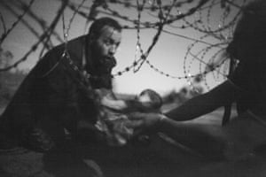 A man handing a child under a barbed wire fence from the village of Horgoš in Serbia to Röszke in Hungary during the European migration crisis in 2015.
