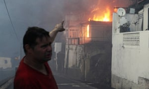 A man gestures at a burning house as a wildfire spreads at Bom Sucesso in Funchal.