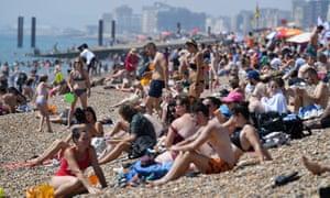 Sun-worshippers crowd the beach at Brighton