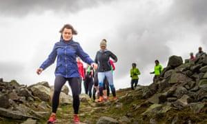 A line of women running down a steep, rocky hillside
