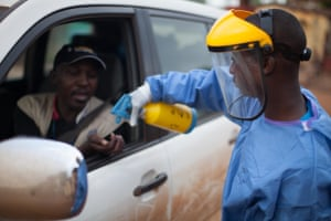 Security in Guinea doesn't check for guns, it checks for temperature - an indicator for Ebola infection. Here a security guard sprays a driver's hands with a chlorine solution that kills the Ebola virus