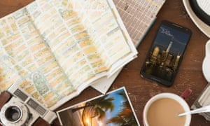 array of a travel related items grouped on a table including a smartphone