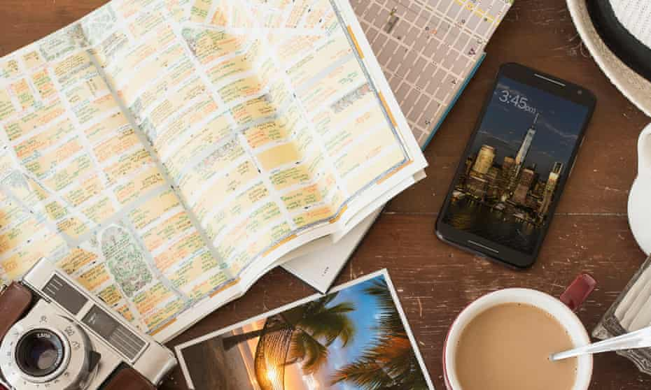 Array of a travel-related items grouped on a table, including a smartphone, map, camera and a mug of tea.