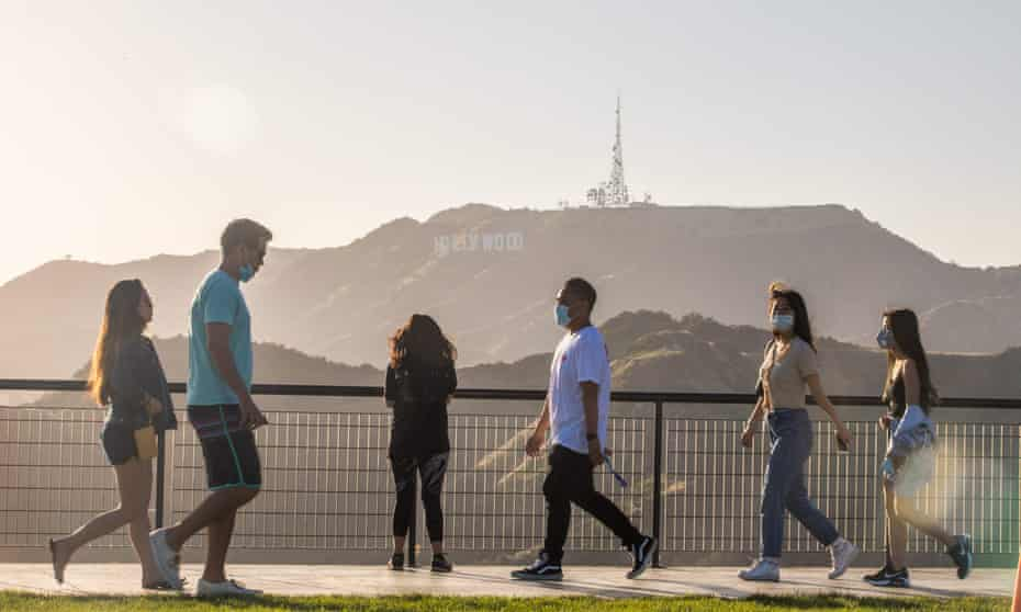 People walk at the Griffith Observatory with a view of the Hollywood sign in Los Angeles.
