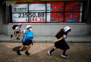 Tokyo, JapanChildren run to school past an electronic board showing Japan's Nikkei average outside a brokerage, amid the coronavirus disease (COVID-19) outbreak