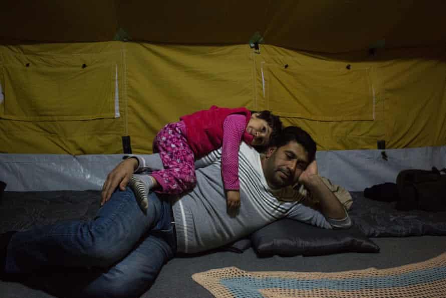 Batul Matlaq, four, lies on her father, Abdulrazzaq.