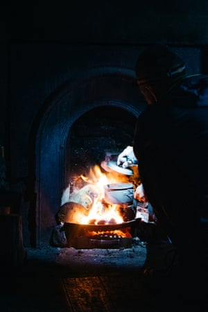 A fire roars in a grate at a bothy. Any luxuries must be carried in, as in the case of this visitor to Glendhu, who brought his own cooking pot when he stopped overnight on his way north to Cape Wrath.