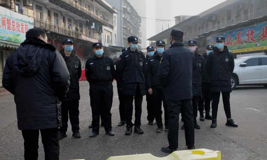 Security guards outside the Huanan wholesale seafood market in Wuhan, central China, where health authorities say the man who died from the new coronavirus had bought food.