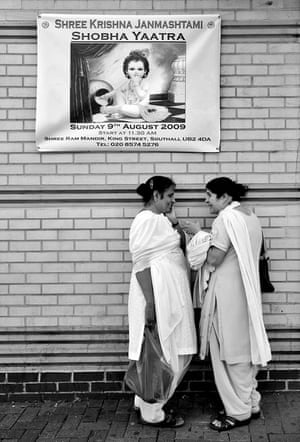Two women talk in the street in Southall, London.