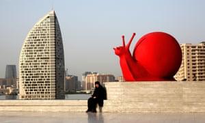 A woman sits by a sculpture of a snail near the Heydar Aliyev Cultural Centre in Baku, Azerbaijan.