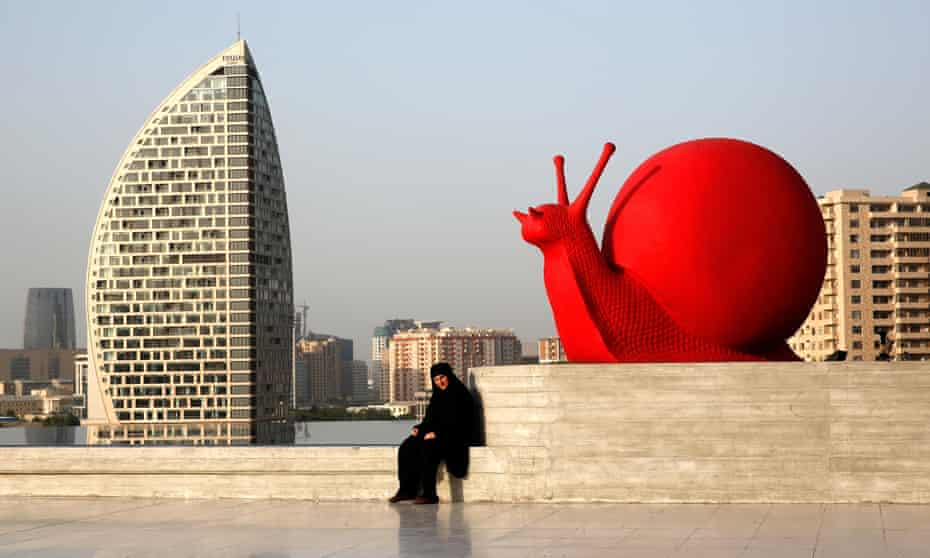 A woman sits by a sculpture of a snail near the Heydar Aliyev Cultural Centre ahead of the first European Games in Baku.