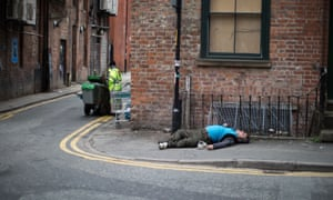 A man lies collapsed on the pavement in Manchester – use of spice is a problem among the homeless.