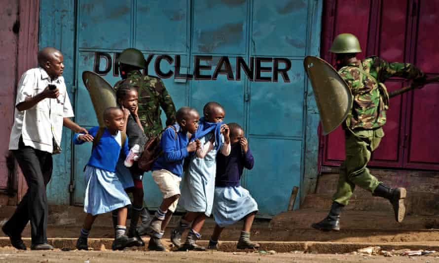 Riot policemen run past school children during a demonstration in Kibera slum, Nairobi.