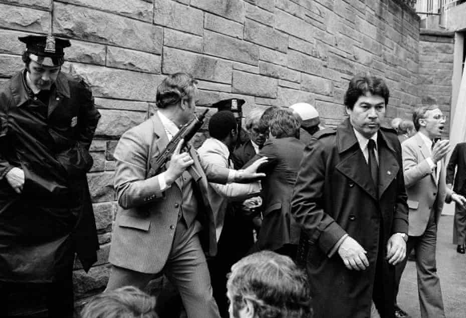 Secret service agents and police officers swarm a gunman, hidden from view, after he attempted an assassination on President Ronald Reagan on 30 March 1981.