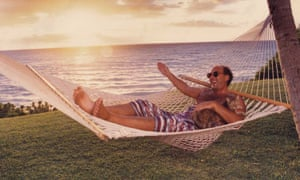 shep gordon relaxing in a hammock by the sea at sunset