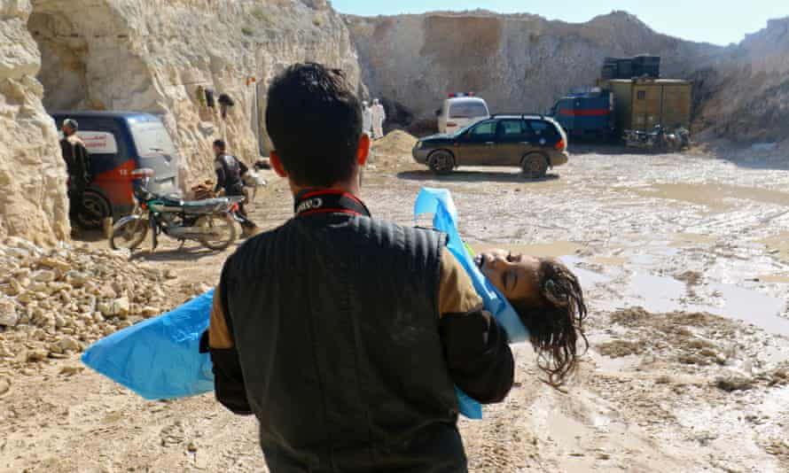 A man carries the body of a child, after what rescue workers described as a suspected gas attack in the town of Khan Sheikhun.
