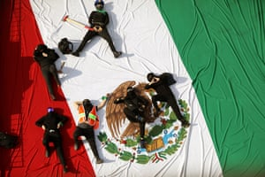 Activists lie on a Mexican flag at the National Polytechnic Institute protesting over women's rights and demanding justice for harassment in the facility