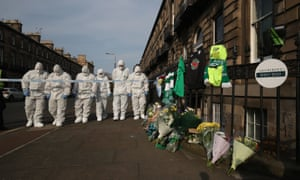 A forensics team searches for clues near floral tributes left for Bradley Welsh at the scene of the shooting in Edinburgh