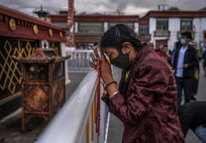A Tibetan Buddhist woman prays in front of the Jokhang Temple in Lhasa