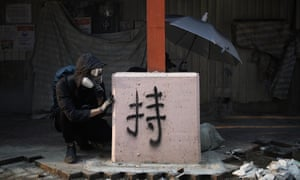 Protesters take cover during a confrontation with police in Hong Kong, 20 October.