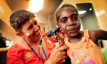 A nurse checking the ear of a young Aboriginal girl