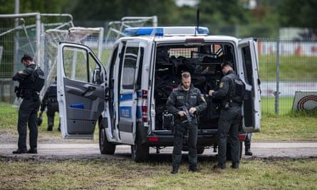 Armed officers by police van