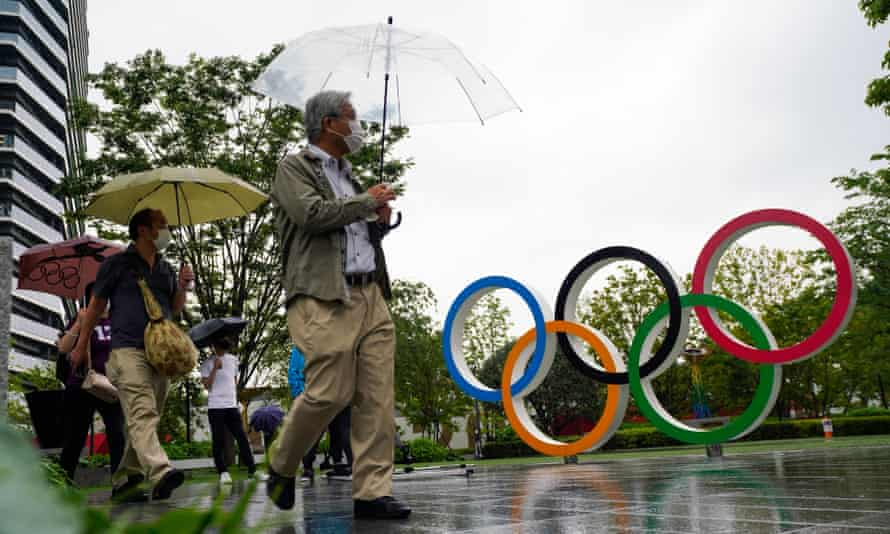 People walk past the Olympic Rings near the new National Stadium in Tokyo, Japan on July 8, 2021.