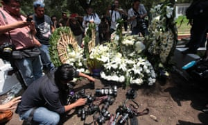 Flowers and cameras on ground at Rubén Espinosa's funeral.