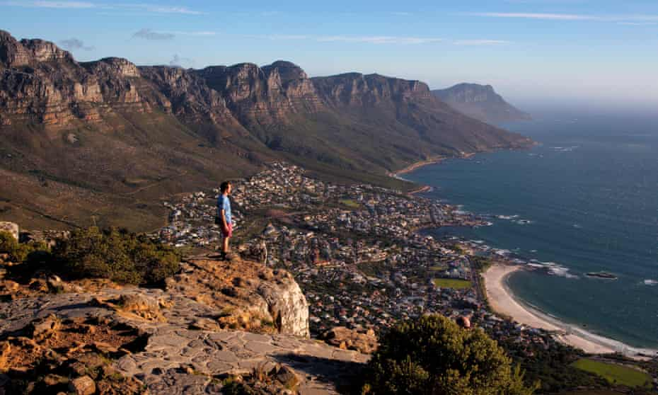 A tourist enjoys the view from the top of Lion's Head above Cape Town