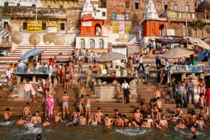 """Varanasi, India. Longitude: 83¡ 00' 92.00"""" Men and boys bathe at the Ahilya Bai Ghat on the banks of the Ganges in Varanasi, one of the holiest cities in India. Despite repeated clean-up efforts by the government since the 1980s, the river remains one of the world's most polluted. About 30,000 bodies a year are cremated on the banks of the Ganges and their ashes scattered into the river"""