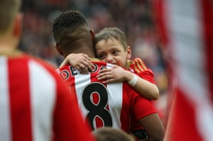 Jermain Defoe carries out young Bradley Lowery as the players take to the pitch.