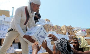 Yemeni workers unload medical aid boxes from a boat