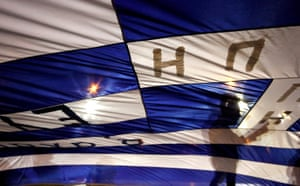 Anti-austerity protesters hold a Greek flag in Athens