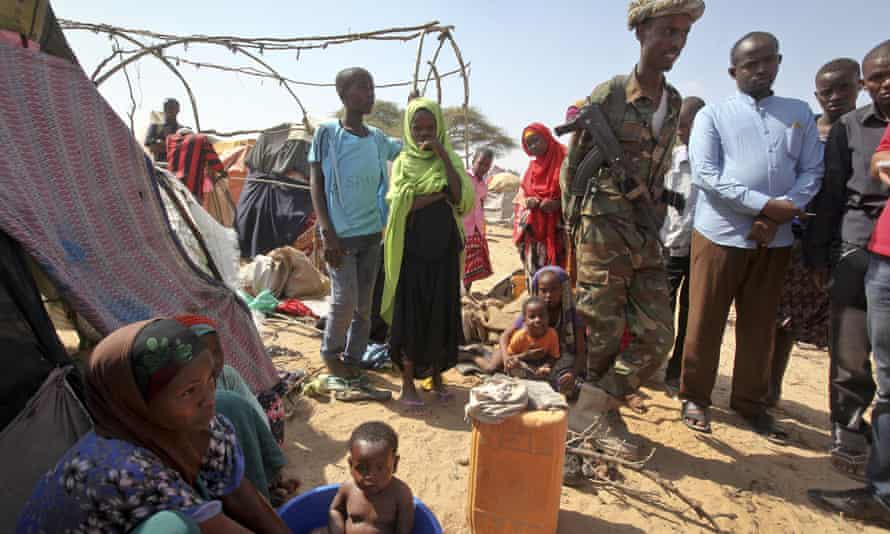 A soldier provides security as people forced from their homes gather at a camp in the Garasbaley area on the outskirts of Mogadishu, Somalia
