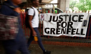 "Pedestrians walk past a sign that reads ""Justice For Grenfell"""